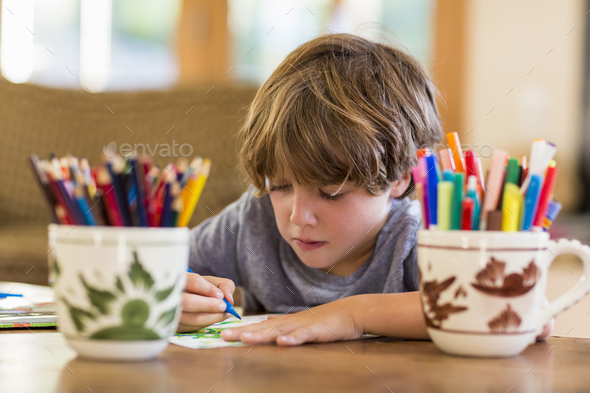 6 year old boy drawing amoung colorful pens - Stock Photo - Images