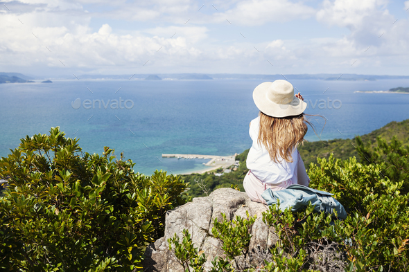 Japanese woman wearing hat sitting on rock on a cliff, ocean in the background. - Stock Photo - Images