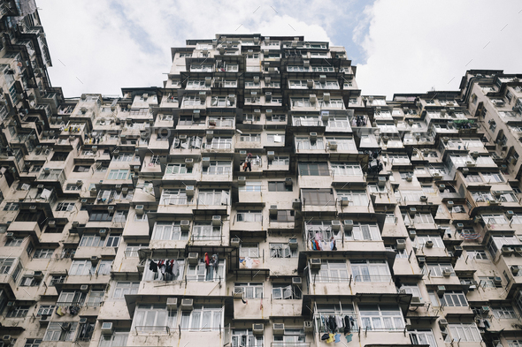 Low angle view of facade of towering residential complex with windows and balconies. - Stock Photo - Images