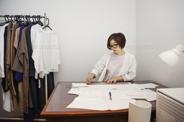 Japanese woman wearing glasses working at a desk in a small fashion boutique. - Stock Photo - Images