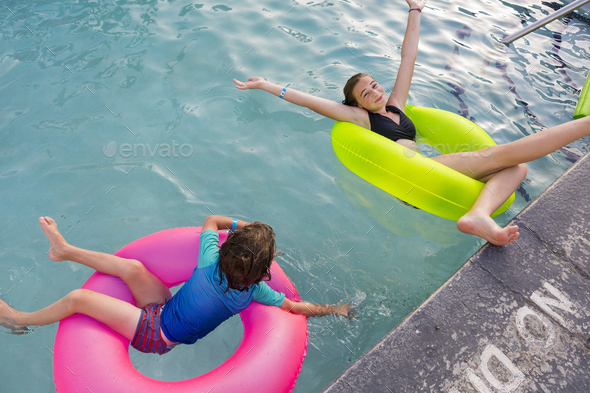 siblings playing in pool with colorful floaties. - Stock Photo - Images