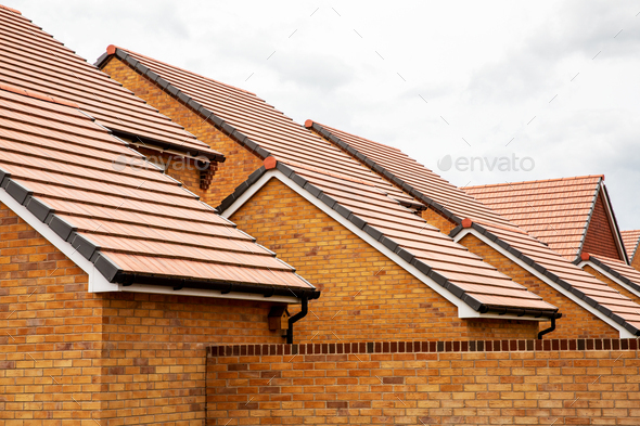 Exterior view of yellow brick row house with yellow roof tiles. - Stock Photo - Images