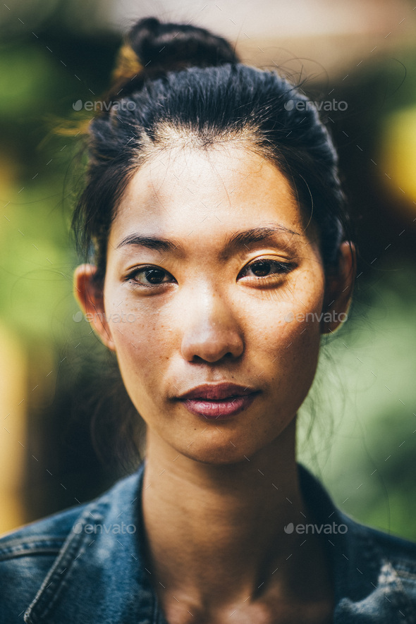 Portrait of a young woman with black hair tied in a top knot, looking at camera. - Stock Photo - Images