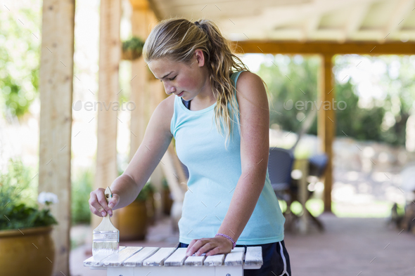 13 year old girl painting outdoor furniture white - Stock Photo - Images