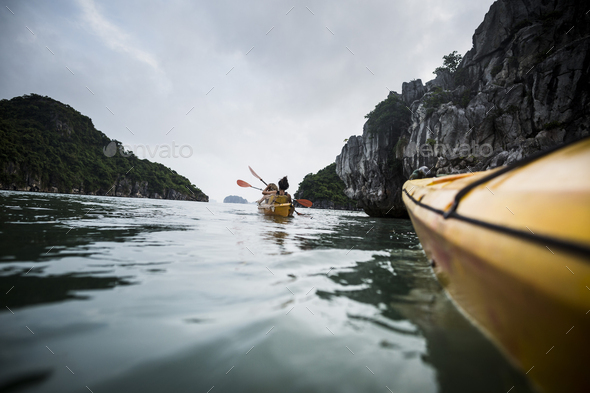 Group of kayakers rowing in a bay amidst limestone karst formations. - Stock Photo - Images