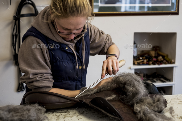 Female saddler standing in workshop, stuffing leather saddle with horse hair. - Stock Photo - Images