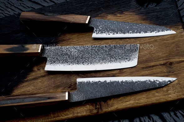 High angle close up of three handmade knives on wooden cutting board. - Stock Photo - Images