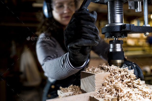 Woman with long brown hair wearing dungarees, safety glasses and ear protectors standing in wood - Stock Photo - Images