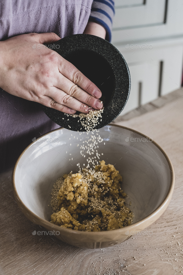 High angle close up of person adding sesame seeds to dough in a mixing bowl. - Stock Photo - Images
