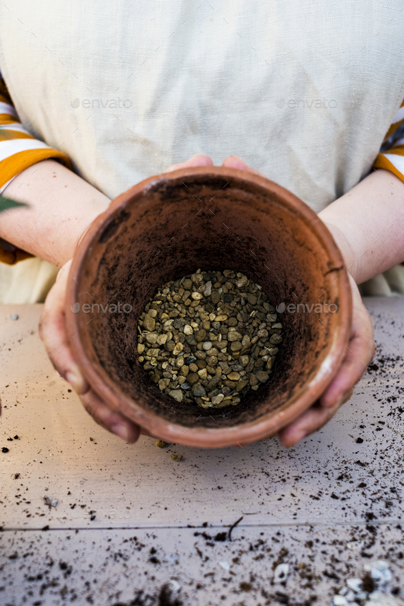 High angle close up of person holding terracotta plant pot with gravel. - Stock Photo - Images