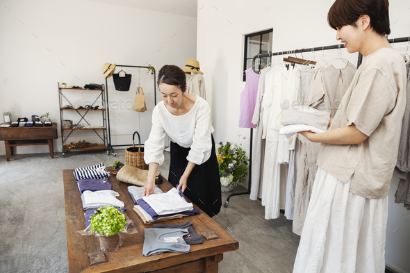 Two Japanese women standing in a small fashion boutique, arranging T-Shirts on a coffee table. - Stock Photo - Images