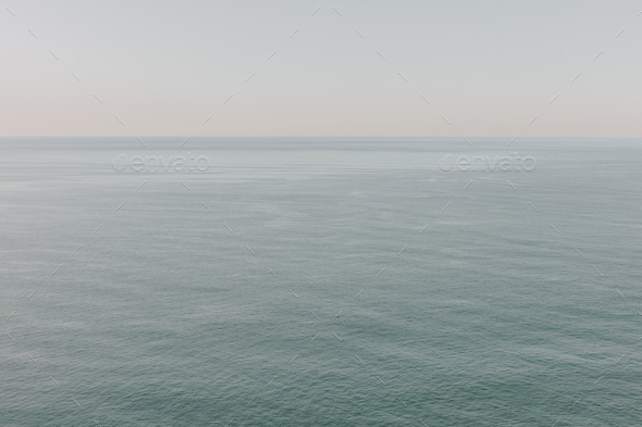 View of calm ocean waters, horizon and sky at dawn, northern Oregon coast - Stock Photo - Images