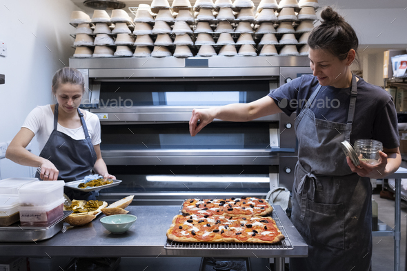 Woman wearing apron standing in an artisan bakery, preparing pizza. - Stock Photo - Images