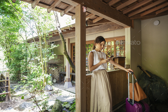 Japanese woman standing on a porch, using mobile phone, holding suitcase and handbag. - Stock Photo - Images