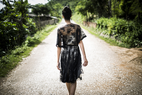 Rear view of woman wearing black lace dress walking down a rural country road. - Stock Photo - Images
