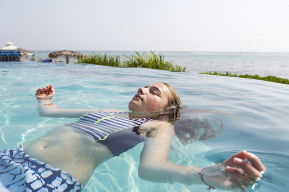 13 year old girl floating in infinity pool - Stock Photo - Images