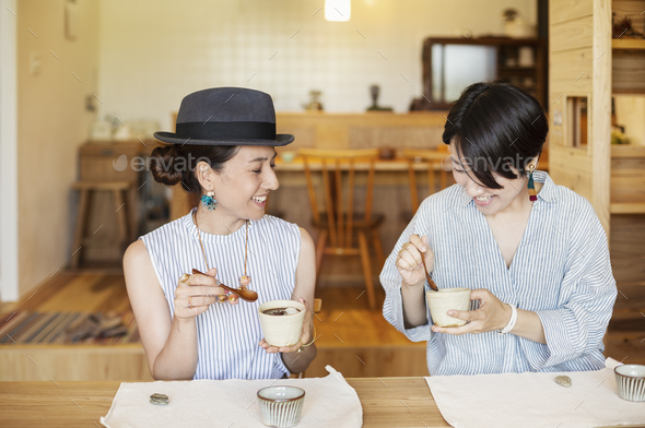 Two smiling Japanese women eating in a vegetarian cafe. - Stock Photo - Images