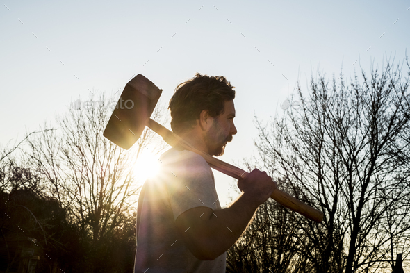 Bearded man walking outdoors at sunset, carrying large wooden mallet on his shoulder. - Stock Photo - Images