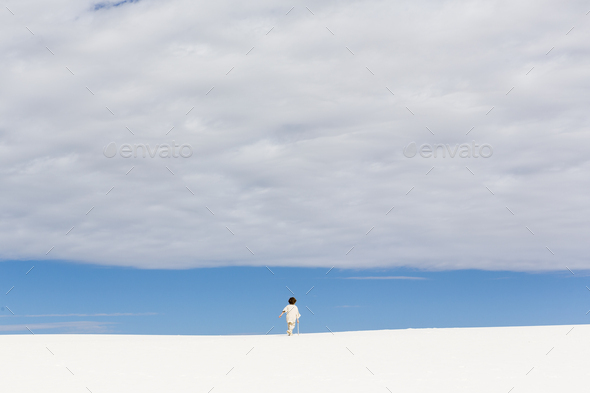6 year old boy walking in white sand dunes, a strip of blue sky on the horizon and thick cloud. - Stock Photo - Images