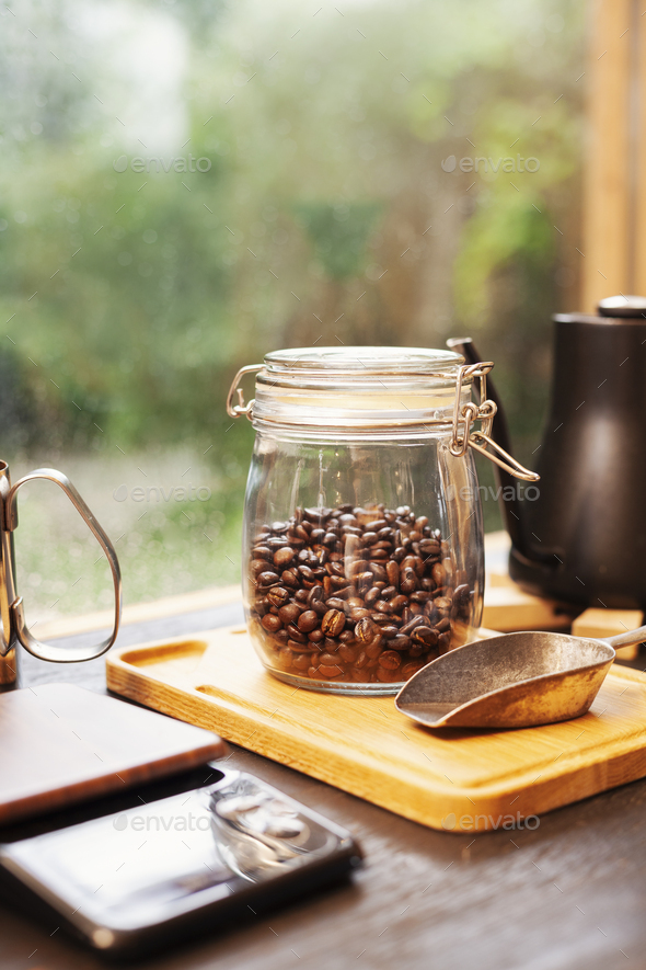 Close up of coffee pot, glass jar with coffee beans and metal coffee shovel on wooden board. - Stock Photo - Images