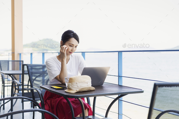 Female Japanese professional sitting on balcony of a co-working space, using laptop computer. - Stock Photo - Images