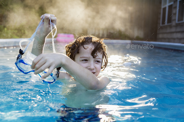 A six year old boy playing in a warm pool, steam rising. - Stock Photo - Images