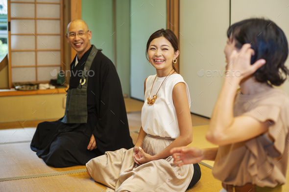 Two Japanese women and Buddhist priest kneeling in Buddhist temple, talking. - Stock Photo - Images