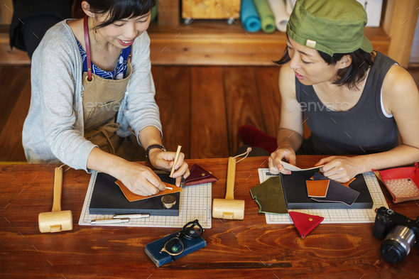 High angle view of two Japanese women sitting at a table, working in a leather shop. - Stock Photo - Images