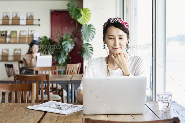 Female Japanese professional sitting at a table in a co-working space, using laptop computer. - Stock Photo - Images
