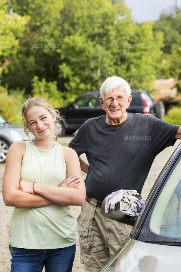 senior grandfather and his 13 year old grand daughter washing a car together in driveway - Stock Photo - Images