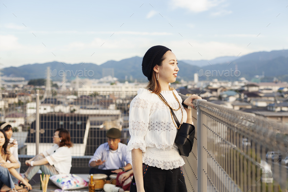 Smiling young Japanese woman standing on a rooftop in an urban setting. - Stock Photo - Images
