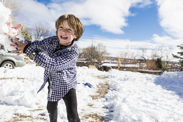 A six year old boy throwing a snowball - Stock Photo - Images