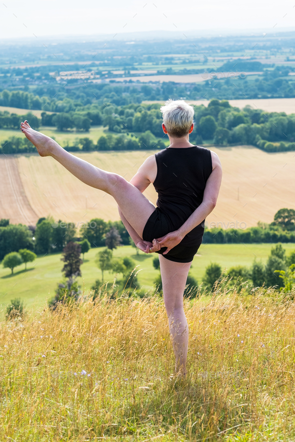 Mature woman taking part in a yoga class on a hillside. - Stock Photo - Images