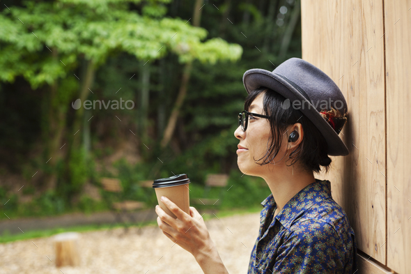 Japanese woman wearing glasses and hat standing outside Eco Cafe, holding paper cup. - Stock Photo - Images