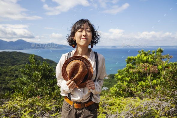 Japanese woman holding hat standing on a cliff, ocean in the background. - Stock Photo - Images