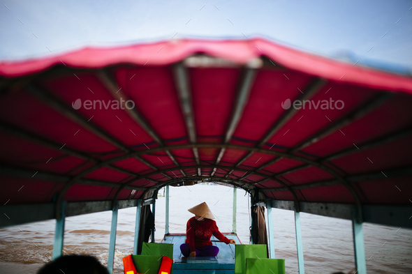 Woman piloting a boat with red canopy through a river. - Stock Photo - Images