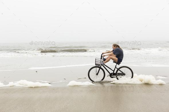 teen girl biking on sand at the beach, St. Simon's Island Georgia - Stock Photo - Images