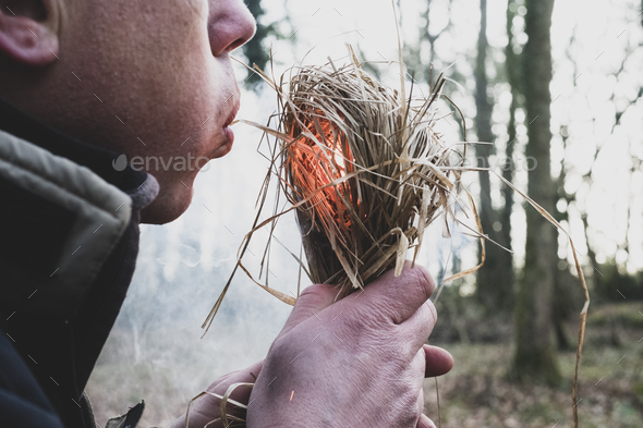 Close up of man blowing on bundle of straw, igniting fire. - Stock Photo - Images