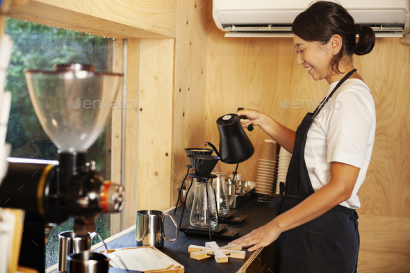 Japanese woman wearing apron standing in an Eco Cafe, preparing coffee. - Stock Photo - Images