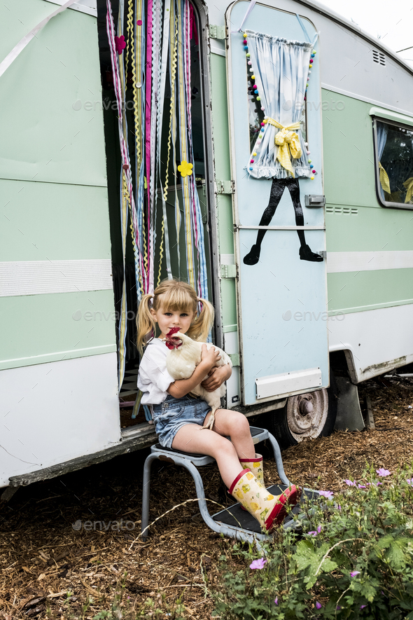Blond girl holding white chicken sitting outside a caravan. - Stock Photo - Images