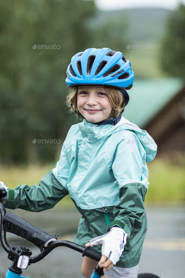 portrait of 5 year old boy wearing rain jacket, straddling his bike - Stock Photo - Images