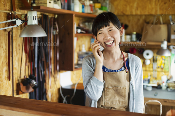 Smiling Japanese woman wearing apron standing in a leather shop, talking on her mobile phone. - Stock Photo - Images