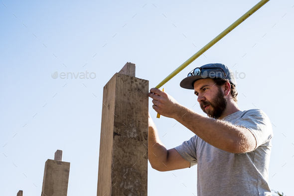 Man wearing baseball cap and sunglasses on building site, using tape measure. - Stock Photo - Images