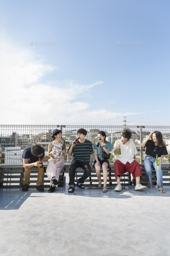 Smiling group of young Japanese men and women sitting on a rooftop in an urban setting. - Stock Photo - Images