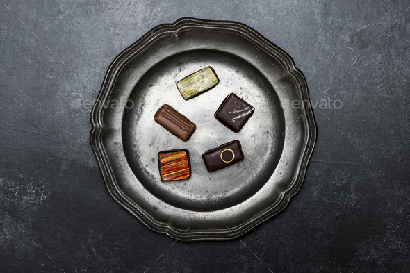 High angle close up of a selection of chocolate pralines on a tin plate on black background. - Stock Photo - Images