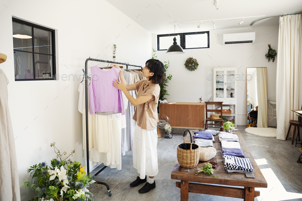 Japanese woman standing in a boutique, looking at clothes on a rail. - Stock Photo - Images