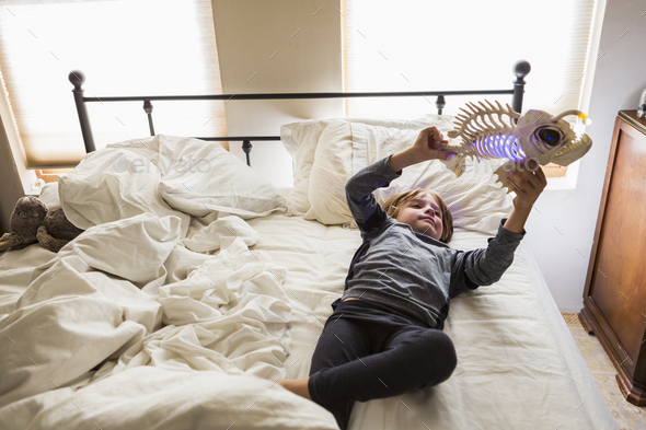 6 year old boy playing with his toys on his bed - Stock Photo - Images
