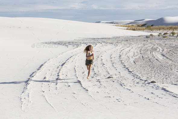 A teenage girl running in the sand, White Sands Nat'l Monument, NM - Stock Photo - Images