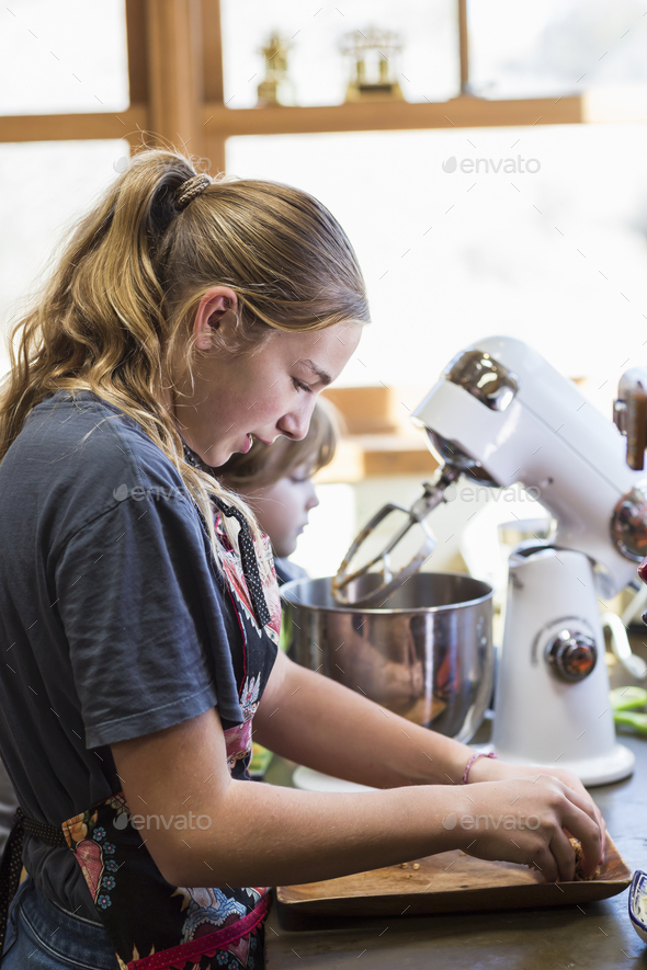 Thirteen year old teenage girl and her 6 year od brother in the kitchen,using a mixing bowl - Stock Photo - Images