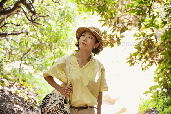 Japanese woman wearing hat hiking in a forest. - Stock Photo - Images